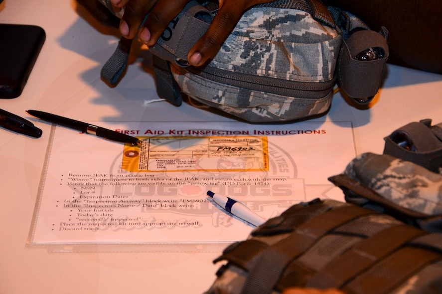 Directions on how to properly inspect and put together a joint first aid kit (JFAK) sits on a table at Al Udeid Air Base, Qatar, June 15, 2016. Each JFAK is hand inspected and signed off by the inspector to ensure each item inside is not expired or close to expiration. (U.S. Air Force photo by Senior Airman Kimberly Nagle)