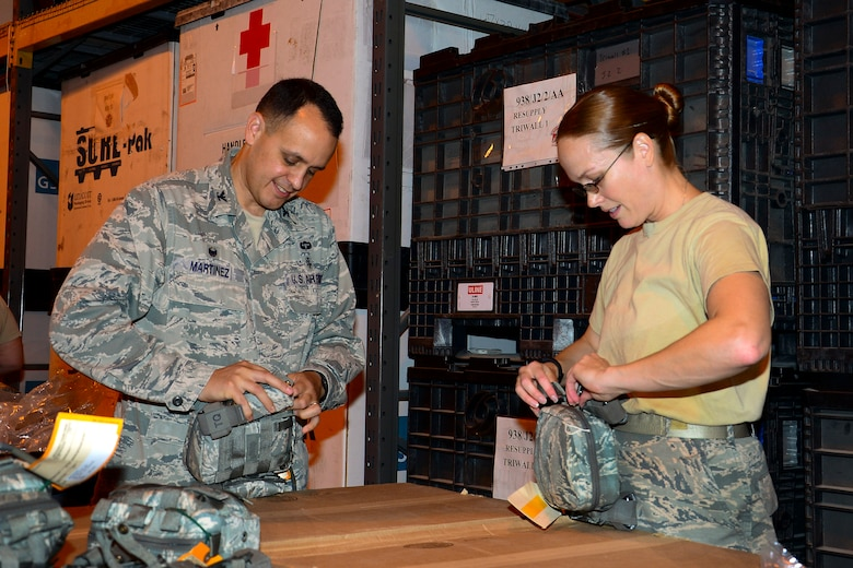 U.S. Air Force Col. Timothy Martinez, 379th Expeditionary Medical Group commander, builds and inspects a joint first aid kit (JFAK) with Tech. Sgt Jennifer Lotan, right, 379th Expeditionary Medical Support Squadron noncommissioned officer in charge of war rescue material, at Al Udeid Air Base, Qatar, June 15, 2016. During the event, the group was able to inspect and build more than 1,000 JFAKs. (U.S. Air Force photo by Senior Airman Kimberly Nagle)