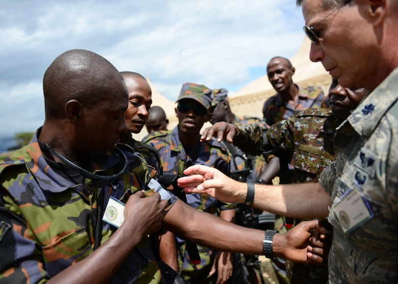 Kenyan and Ugandan Defense Forces are instructed by Lt. Col. Mark Prete, tactical combat casualty care instructor, 104th Fighter Wing Massachusetts Air National Guard, on how to apply a tourniquet during African Partnership Flight Kenya at Laikipia Air Base, Kenya, June 20, 2016. More than 50 U.S. Air Force Airmen participated in the first African Partnership Flight in Kenya. The APF is designed for U.S. and African partner nations to work together in a learning environment to help build expertise and professional knowledge and skills. (U.S. Air Force photo by Tech. Sgt. Evelyn Chavez/Released)