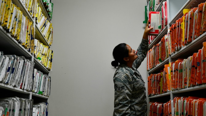 Airman 1st Class Laura Gaitan, 31st Medical Support Squadron medical records technician, retrieves a Team Aviano member's medical record for processing, June 20, 2016, at Aviano Air Base, Italy. The 31st MDSS medical records team stores and processes both electronic and paper medical records for in- and out-processing members. (U.S. Air Force photo by Airman 1st Class Cary Smith/Released)