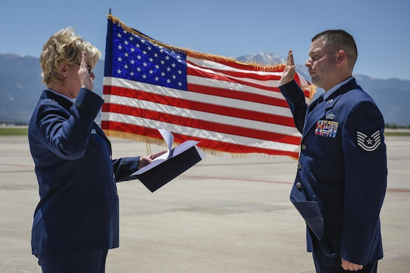 PETERSON AIR FORCE BASE, Colo. - Tech. Sgt. Sean Dastas, 21st Operations Support Squadron, right, recites the oath of enlistment back to his mother, Capt. Stephanie Lawton, 9th Medical Group at Beale Air Force Base, Calif., June 15, 2016. Dastas was reenlisted for another four years by his mother, who traveled from California for the occasion. (U.S. Air Force photo by Senior Airman Rose Gudex)