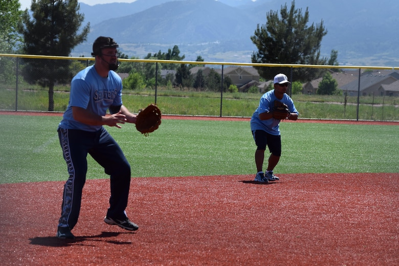 Staff Sgt. Matthew Brown, 361st Training Squadron, and Master Sgt. Junicio Cacal, 82nd Aerospace Medical Squadron, prepare to field a hit at military softball tournament in Colorado, June 13, 2016. The Sheppard Senators, Sheppard Air Force Base's men's varsity softball team, ranks first out of 57 Varsity 'B' military teams from around the country.