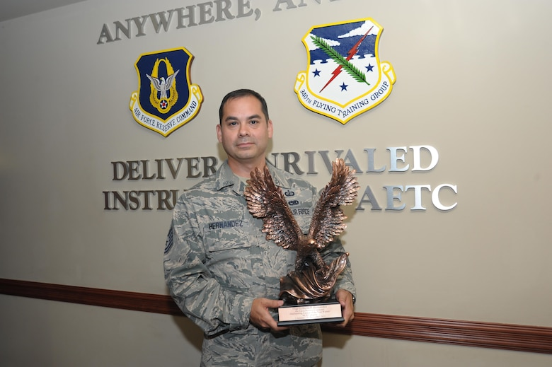 Technical Sergeant Gilberto Hernandez, 340th Flying Training Group, non-commissioned officer of the year, poses with his award June 15, at Joint Base San Antonio-Randolph. Hernandez led the processing of more than 25,000 military pay transactions with a 98.6 percent accuracy rate in 2015.