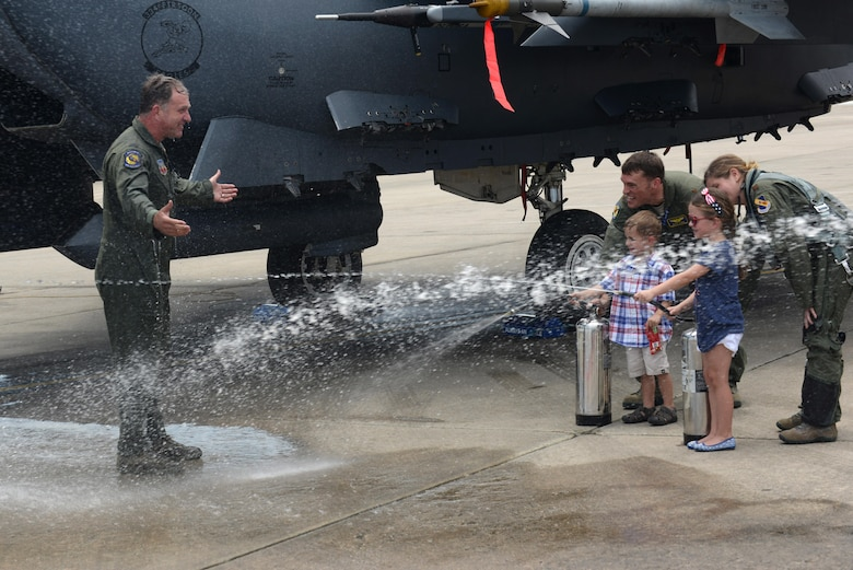 Col. Mark Slocum, 4th Fighter Wing commander, is hosed down by his children following his final flight in an F-15E Strike Eagle, June 16, 2016, at Seymour Johnson Air Force Base, North Carolina. Slocum will be promoted to brigadier general on June 29, 2016, before departing for a position at Royal Air Force Mildenhall, England. (U.S. Air Force photo/Airman 1st Class Ashley Williamson)