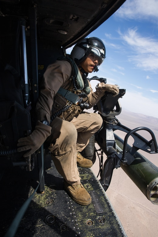 """Lance Cpl. Servando Avila, a crew chief with Marine Light Attack Helicopter Squadron (HMLA) 267 """"Stingers"""" and a Houston native, observes the location of a nearby aircraft above Marine Corps Air Ground Combat Center Twentynine Palms, Calif., June 10. Marines with HMLA-267 supported Marines with 3rd Battalion, 7th Marine Regiment during a close-air-support training mission aboard the combat center. (U.S. Marine Corps photo by Sgt. Lillian Stephens/Released)"""