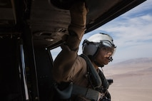 """Lance Cpl. Servando Avila, a crew chief with Marine Light Attack Helicopter Squadron (HMLA) 267 """"Stingers"""" and a Houston native, looks out the door of a UH-1Y Huey during a flight over Marine Corps Air Ground Combat Center Twentynine Palms, Calif., June 10. Marines with HMLA-267 supported Marines with 3rd Battalion, 7th Marine Regiment, during a close-air-support training mission aboard the combat center. (U.S. Marine Corps photo by Sgt. Lillian Stephens/Released)"""