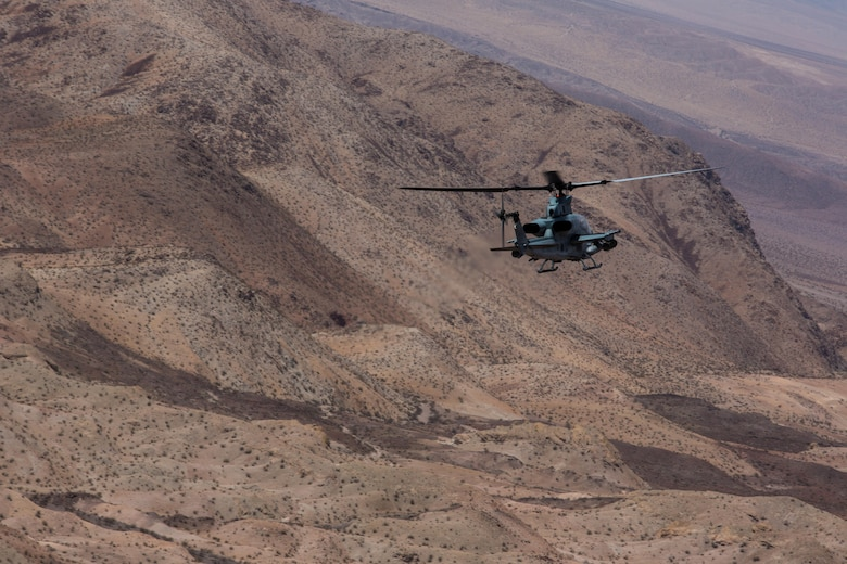 """An AH-1Z Viper with Marine Light Attack Helicopter Squadron (HMLA) 267 """"Stingers"""" maneuvers to assault a simulated target aboard Marine Corps Air Ground Combat Center Twentynine Palms, Calif., June 10. Marines with HMLA-267 supported Marines with 3rd Battalion, 7th Marine Regiment, during a close-air-support training mission aboard the combat center. (U.S. Marine Corps photo by Sgt. Lillian Stephens/Released) (U.S. Marine Corps photo by Sgt. Lillian Stephens/Released)"""
