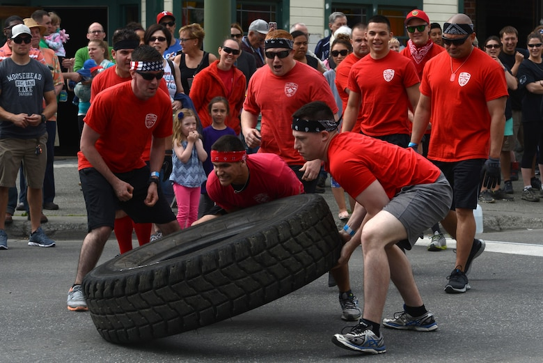 Two members of the 'Firedawgs,' Joint Base Elmendorf-Richardson Fire Department team, flip a tire as part of the Hero Games during the Downtown Summer Solstice Festival in Anchorage, Alaska, June 18, 2016. Each team chose two members to flip a tire across a set distance then roll it back. The Hero Games is a friendly competition between Alaska's first responders with challenges that require balance, strength and teamwork. (U.S. Air Force photo Airman 1st Class Christopher R. Morales)