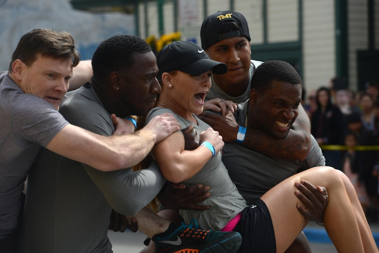 Five members of the 'The Bios,' from the Joint Base Elmendorf-Richardson Hospital, perform a body carry as part of the Hero Games during the Downtown Summer Solstice Festival in Anchorage, Alaska, June 18, 2016. The four-part relay consisted of sprinting, weaving through cones, hula-hooping and the infamous body carry. The Hero Games is a friendly competition between Alaska's first responders with challenges that require balance, strength and teamwork. (U.S. Air Force photo Airman 1st Class Christopher R. Morales)