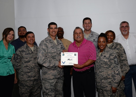 "Eloy Salazar, center, 47th Logistics Readiness Flight Traffic Management Office contracting officer representative, accepts the ""XLer of the Week"" award from Col. Eric Shafa, left, 47th Mission Support Group commander, and Chief Master Sgt. Erica Shipp, right, 47th MSG superintendent, here, June 15, 2016. The XLer is a weekly award chosen by wing leadership and is presented to those who consistently make outstanding contributions to their unit and Laughlin. (U.S. Air Force photo/Senior Airman Jimmie D. Pike)"
