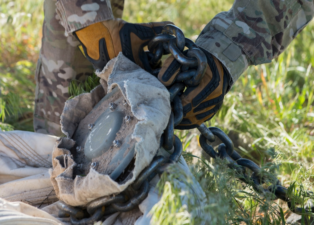 An airman from the 366th Civil Engineer Squadron wraps a chain around an inert GBU-12 Paveway II's parachute in preparation for removal during a range clearance at Saylor Creek Range Complex, Idaho, May 9, 2016. The 366th Fighter Wing at Mountain Home Air Force Base operates, maintains and develops the Mountain Home, Idaho, Range Complex which is comprised of 7,400 square miles of associated airspace and 122,000 acres of land space used for two air-to-ground training ranges, five no-drop target complexes and 30 multi-size electronic combat sites. (U.S. Air Force photo by Airman 1st Class Chester Mientkiewicz/Released)