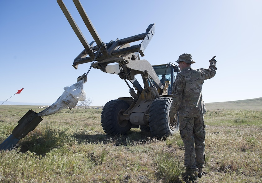 Airmen from the 366th Civil Engineer Squadron extract inert explosives using a shovel loader with fork attachments during a range clearance at Saylor Creek Range Complex, Idaho, May 9, 2016. The 366th Fighter Wing at Mountain Home Air Force Base, Idaho operates, maintains and develops the Mountain Home Range Complex which is comprised of 7,400 square miles of associated airspace and 122,000 acres of land space used for two air-to-ground training ranges, five no-drop target complexes and 30 multi-size electronic combat sites. (U.S. Air Force photo by Airman 1st Class Chester Mientkiewicz/Released)