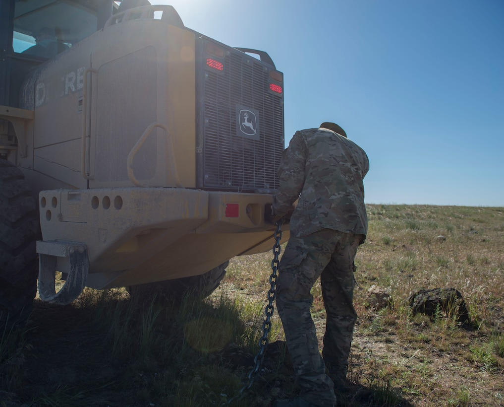 An airman from the 366th Civil Engineer Squadron attaches a chain to a shovel loader in preparation for removal of inert GBU-12 Paveway II during a range clearance at Saylor Creek Range Complex, Idaho, May 9, 2016. The GBU-12s were dropped during training exercises to improve fighter pilots' accuracy. (U.S. Air Force photo by Airman 1st Class Chester Mientkiewicz/Released)