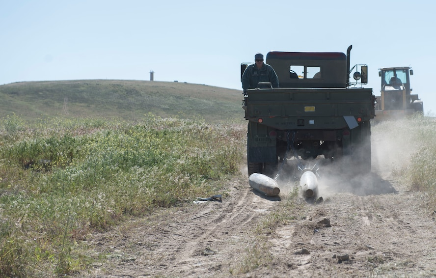 Members from the 366th Civil Engineer Squadron drag inert explosives behind a five-ton truck as airmen gather explosive ordnance during a range clearance at Saylor Creek Range Complex, Idaho, May 9, 2016. The range clearance is a quarterly event held by explosive ordnance disposal ensuring improved safety to individuals training there. (U.S. Air Force photo by Airman 1st Class Chester Mientkiewicz/Released)