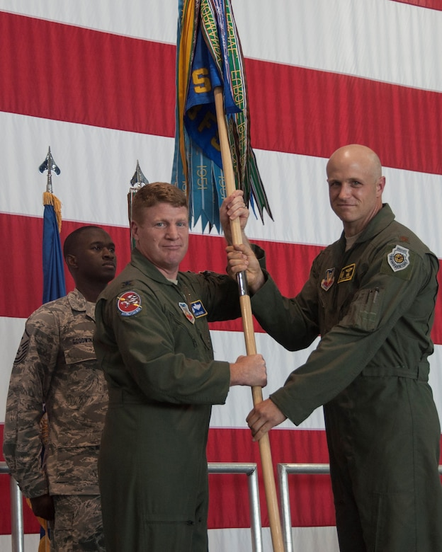 Col. James McCune, 495th Fighter Group commander, left, hands the guidon to Maj. Jeremiah Parvin, 358th Fighter Squadron new commander, during the change of command ceremony in the A-10 hangar at Whiteman Air Force Base, June 21, 2016. One of the oldest military traditions is the passing of a unit flag to symbolize the passing of authority from the outgoing commander to the new commander. (U.S. Air Force photo by Senior Airman Missy Sterling/Released)