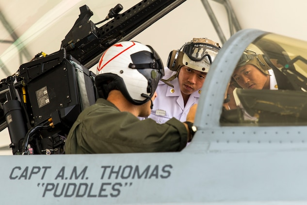 U.S. Marine Corps Capt. Daniel Lane, a pilot with Marine Fighter Attack Squadron (VMFA) 122, shows two Japan Maritime Self-Defense Force aviation officer cadets inside the cockpit of an F/A-18C during a Japanese Officer Exchange Program tour at Marine Corps Air Station Iwakuni, Japan, June 17, 2016. Hosted by Marine Aircraft Group 12, the exchange program aims to better the understanding and working relationships between U.S. and Japanese pilots. During the visit, 30 students from the JMSDF Ozuki Aviation Training Squadron from JMSDF Ozuki Air Base, Shimonoseki, toured the air station to see up close F/A-18C Hornets belonging to Marine Fighter Attack Squadron 122, took turns flying an F/A-18 flight simulator and learned MAG-12's mission, organization, equipment, operations and flight training. (U.S. Marine Corps photo by Lance Cpl. Aaron Henson/Released)
