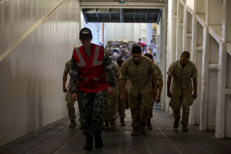 An Australian sailor guides U.S. Marines to an upper deck aboard the HMAS Adelaide at Port of Brisbane, Queensland, Australia, June 16, 2016. This marks the first time Marines and sailors from Marine Rotational Force - Darwin have embarked in such numbers on an Australian HMAS. This opportunity allows for MRF-D to expand the partnership capabilities with our Australian allies. The Marines are with 1st Battalion, 1st Marine Regiment, MRF-D, and the Australians are with HMAS Adelaide.