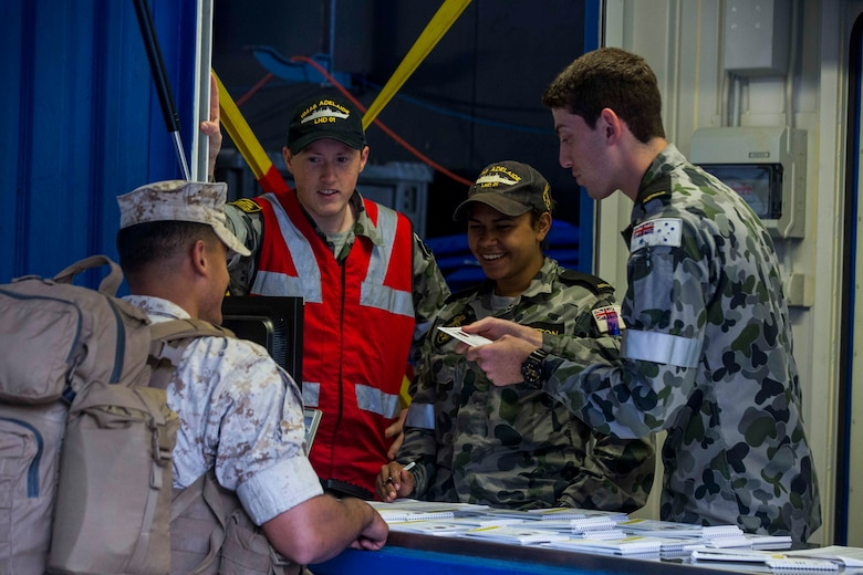 U.S. Marines receive a welcome aboard booklet upon arrival to the HMAS Adelaide at Port of Brisbane, Queensland, Australia, June 16, 2016. This marks the first time Marines and sailors from Marine Rotational Force - Darwin have embarked in such numbers on an Australian HMAS. This opportunity allows for MRF-D to expand the partnership capabilities with our Australian allies. The Marines are with 1st Battalion, 1st Marine Regiment, MRF-D, and the Australians are with HMAS Adelaide.