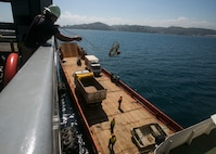 A crew member aboard USNS Sacagawea (T-AKE 2) throws a line to a barge as part of the process of preparing to move supplies from ship to ship. Sacagawea is a Marine Prepositioning Force ship responsible for transporting Task Force Koa Moana to various countries in the Asia-Pacific region to support their mission to increase interoperability and relations. The Marines and Sailors with the task force are originally assigned to I and III Marine Expeditionary Force.