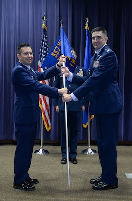 Col. William Carle, 557th Weather Wing commander, passes the guidon to Col. Thomas Blazek as he assumes command of the 1st Weather Group in the 557th Weather Wing auditorium June 21 at Offutt Air Force Base, Neb. (U.S. Air Force by Zachary Hada)