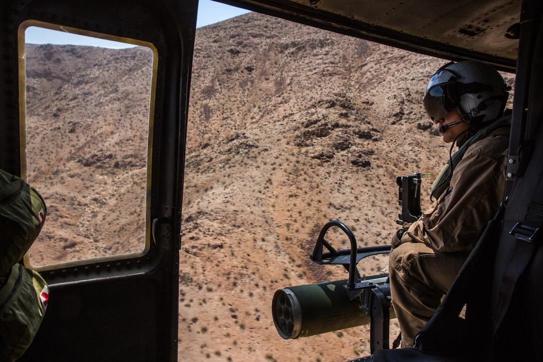 """Lance Cpl. Justin Fry, a crew chief with Marine Light Attack Helicopter Squadron (HMLA) 267 """"Stingers"""" and a Van Vleck, Texas, native, scans the terrain from a UH-1Y Huey while it performs tactical maneuvers aboard Marine Corps Air Ground Combat Center Twentynine Palms, Calif., June 10. Marines with HMLA-267 supported Marines with 3rd Battalion, 7th Marine Regiment, during a close-air-support training mission aboard the combat center. (U.S. Marine Corps photo by Sgt. Lillian Stephens/Released)"""