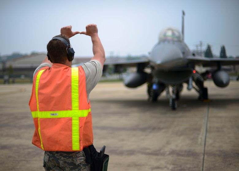 Tech. Sgt. Adam Skadsberg, 148th Aircraft Maintenance Unit weapons one-man, signals to an F-16 Fighting Falcon pilot, June 21, 2016, at Osan Air Base, Republic of Korea. Skadsberg was part of a three-man crew performing the inspection, and was responsible for communicating with the pilots while his teammates inspected each aircraft. (U.S. Air Force photo by Senior Airman Victor J. Caputo/Released)