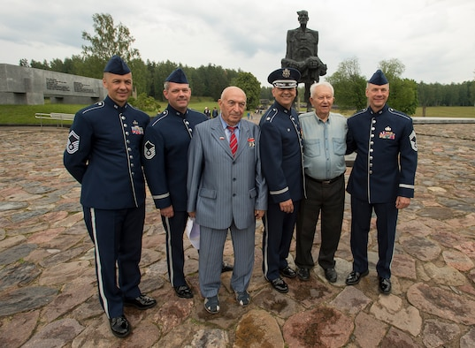 """From left, U.S. Air Force Senior Master Sgt. Vladimir Tchekan, U.S. Air Forces in Europe Band's trombone player; U.S. Air Force Master Sgt. Dave Dell, USAFE Band trumpet player; Vladimir Yarygin, former submariner for the Soviet Union; Lt. Col. Mike Mench, USAFE Band commander; Grigory, former Air Force wing commander for the Soviet Union; and Chief Master Sgt. Mark Burditt, USAFE Band chief enlisted manager, stand for a photograph in front of the """"Unbowed Man"""" statue June 20, 2016, in Khatyn Memorial, Belarus. (U.S. Air Force photo/Technical Sgt. Paul Villanueva II)"""