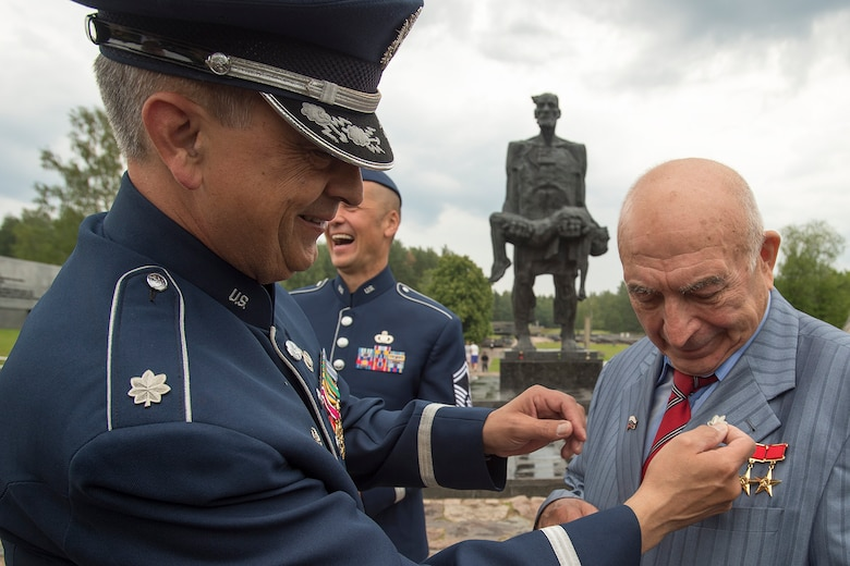 U.S. Air Force Lt. Col. Mike Mench, U.S. Air Forces in Europe Band commander, places a silver oak leaf on Vladimir Yarygin, a former submariner for the Soviet Union, June 20, 2016, in Khatyn Memorial, Belarus. While in Belarus, 13 bandsmen performed at events in Minsk and surrounding communities to commemorate the alliance that ended the greatest conflict of the 20th Century. (U.S. Air Force photo/Technical Sgt. Paul Villanueva II)