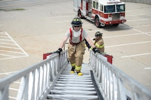 U.S. Air Force Col. Marty Reynolds, 55th Wing commander, participates in a fire rescue exercise at building 382 with firefighters assigned to the 55th Civil Engineer Squadron at Offutt Air Force Base, Neb., June 21, 2016. The exercise provided firsthand experience what tools and techniques are needed to perform the duties of an Offutt firefighter. (U.S. Air Force photo by Zachary Hada)