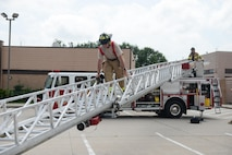U.S. Air Force Chief Master Sgt. Michael Morris, 55th Wing command chief, participates in a fire rescue exercise at building 382 with firefighters assigned to the 55th Civil Engineer Squadron at Offutt Air Force Base, Neb., June 21, 2016.  The exercise provided firsthand experience with tools and techniques that are needed to perform the duties of an Offutt firefighter. (U.S. Air Force photo by Zachary Hada)