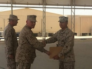 """Cpl. Daniel """"D.J."""" Deleon, right, is presented an award by his father, Maj. James Ramsey, while deployed in Bahrain in June 2015. Throughout their time in the Marine Corps, Ramsey and Deleon found themselves deployed or stationed together multiple times. (Courtesy photo/Released)"""