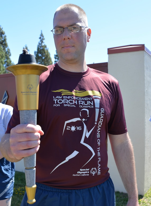 "Staff Sgt. Steven Sawyer, 60th Security Forces Squadron police services NCO in charge and event participant, receives ""The Flame of Hope,"" an olympic torch passed from one law enforcement agency to the next, from the Fairfield Police Department, June 23 at Travis Air Force Base, California. The 60th SFS then ran the torch from the Main gate to the North Gate as part of the Northen California Special Olympics Summer Games at the University of California in Davis, California."