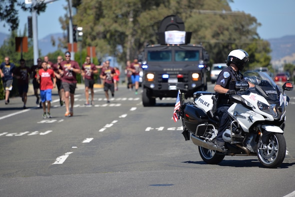 """Members from the 60th Security Forces Squadron receive """"The Flame of Hope,"""" an olympic torch passed from one law enforcement agency to the next, from the Fairfield Police Department, June 23 at Travis Air Force Base, California. The 60th SFS then ran the torch from the Main gate to the North Gate as part of the Northen California Special Olympics Summer Games opening ceremony at the University of California in Davis, California."""
