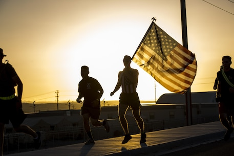 A Marine with Communications Training Battalion, Marine Corps Communication-Electronics School, runs with the national colors during the battalion's Sunset Run aboard the Marine Corps Air Ground Combat Center, Twentynine Palms, Calif., June 17, 2016. (Official Marine Corps photo by Lance Cpl. Levi Schultz/Released)