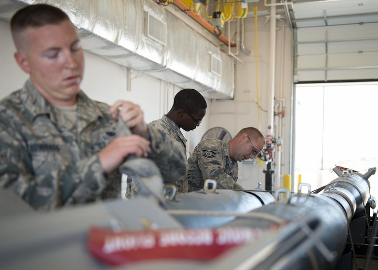 From left to right: Staff Sgt. Aaron, Airman James and Tech. Sgt. Douglas, 49th Maintenance Squadron munitions crew chiefs, secure Guided Bomb Units-12 Paveway II bombs to an ammunition trailer June 21 at Holloman Air Force Base, N.M. The 49th MXS provides GBU-12s and other ammunition to the 49th Wing, as well as a multitude of tenant units in support of training, testing and international flying missions. (Last names are withheld due to operational requirements. U.S. Air Force photo by Senior Airman BreeAnn Sachs)