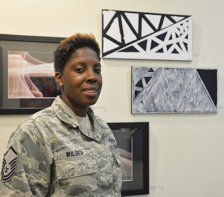 Master Sgt. Bahiya Wilder, 60th Operations Support Squadron aircrew flight equipment quality assurance flight chief, stands with two of her paintings June 22 at a gallery at the Solano Town Center Mall in Fairfield, Calif.