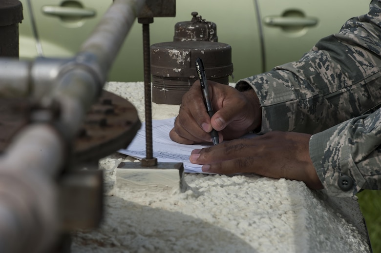 U.S. Air Force Tech. Sgt. Camarius Johnson, 18th Logistics Readiness Squadron fuels quality assurance evaluator, completes an organizational tank inspection June 21, 2016, at Kadena Air Base, Japan. Part of the inspection process involves getting paperwork signed by the evaluators. (U.S. Air Force photo by Airman 1st Class Lynette M. Rolen)