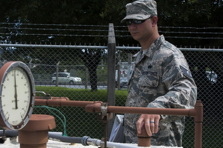 U.S. Air Force Tech. Sgt. Matthew Young, 18th Logistics Readiness Squadron fuels quality assurance evaluator, conducts an organizational tank inspection June 21, 2016, at Kadena Air Base, Japan. The inspection included checking the safety of tanks for the surrounding environment and security from tampering. The tanks help fuel a lift station, which prevents flooding in housing and the local community. (U.S. Air Force photo by Airman 1st Class Lynette M. Rolen)