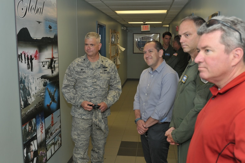Col. Shawn Clouthier (left), 109th Airlift Wing commander, shows Gabe Camarillo, Brig. Gen. Bradley Swanson and Chris Swadener some photos displayed showcasing the wing's mission during a tour of Stratton Air National Guard Base, New York, on June 22, 2016. Camarillo is the Assistant Secretary of the Air Force for Manpower and Reserve Affairs; Swanson is the Director of Plans and Programs at the Air National Guard Readiness Center; and Swadener is the Associate Director of Operations for the Air National Guard. (U.S. Air National Guard photo by Staff Sgt. Benjamin German/Released)
