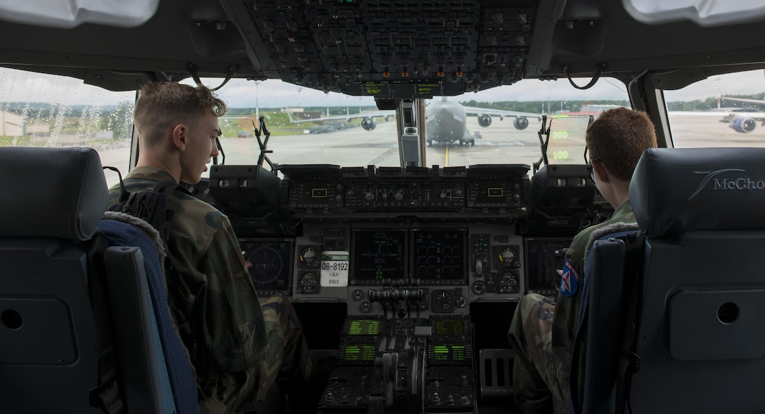 Two Civil Air Patrol cadets sit in the flight deck of a C-17A Globemaster III aircraft during a tour June 21, 2016, at Ramstein Air Base, Germany. The 721st Aircraft Maintenance Squadron hosted this portion of the tour, allowing the cadets to see inside the plane. CAP toured Ramstein from June 18 to 24, and visited squadrons associated with all three wings on base to get a glimpse of what life is like as an Airman. (U.S. Air Force photo/Airman 1st Class Tryphena Mayhugh)