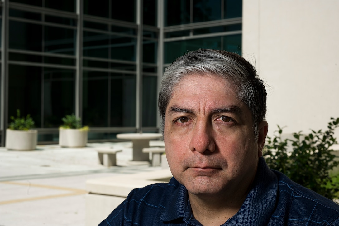 Alfredo Guerrero sits in front of the Defense Threat Reduction Agency building at Fort Belvoir, Va., on June 10, 2016, where he works as the anti-terrorism program manager. Guerrero was on top of Bldg. 131 of the Khobar Towers complex in Dharan, Saudi Arabia, on June 25, 1996, when he spotted a suspicious large gas truck drive toward the building. When the truck parked and two men jumped out and got into a car that had been following them, Guerrero and two other Airmen immediately began evacuating the building. A short time later the truck exploded, killing 19 Airmen and injuring more than 350 people. (U.S. Air Force photo/Staff Sgt. Christopher Gross)