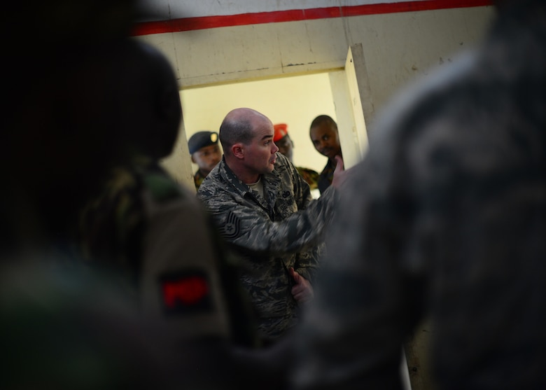 U.S. Air Force Tech. Sgt. Andrew Acosta, 818th Mobility Support Advisory Squadron security forces advisor, helps Kenyan Defense Forces prepare for close quarter combat training during African Partnership Flight Kenya at Laikipia Air Base, Kenya, June 23, 2016. More than 50 U.S. Air Force Airmen participated in the first APF in Kenya. The APF is designed for U.S. and African partner nations to work together in a learning environment to help build expertise and professional knowledge and skills. (U.S. Air Force photo by Tech. Sgt. Evelyn Chavez/Released)