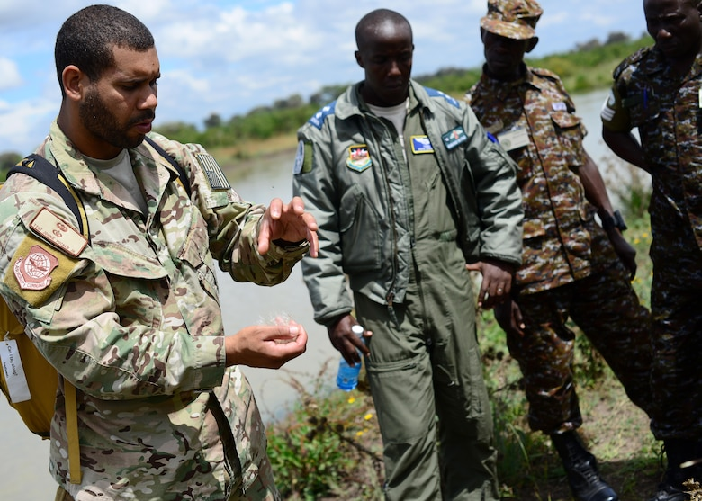 U.S. Air Force Tech. Sgt. Johnie Tucker, 818th Mobility Support Advisory Squadron survival evasion resistance and escape specialist air advisor, discusses survival techniques with Kenyan Defense Force members at Laikipia Air Base, Kenya, June 23, 2016. More than 50 U.S. Air Force Airmen participated in the first African Partnership Flight in Kenya. The APF is designed for U.S. and African partner nations to work together in a learning environment to help build expertise and professional knowledge and skills in key areas such as personnel recovery command and control, survival and evasion principles and tactical combat casualty care. (U.S. Air Force photo by Tech. Sgt. Evelyn Chavez/Released)