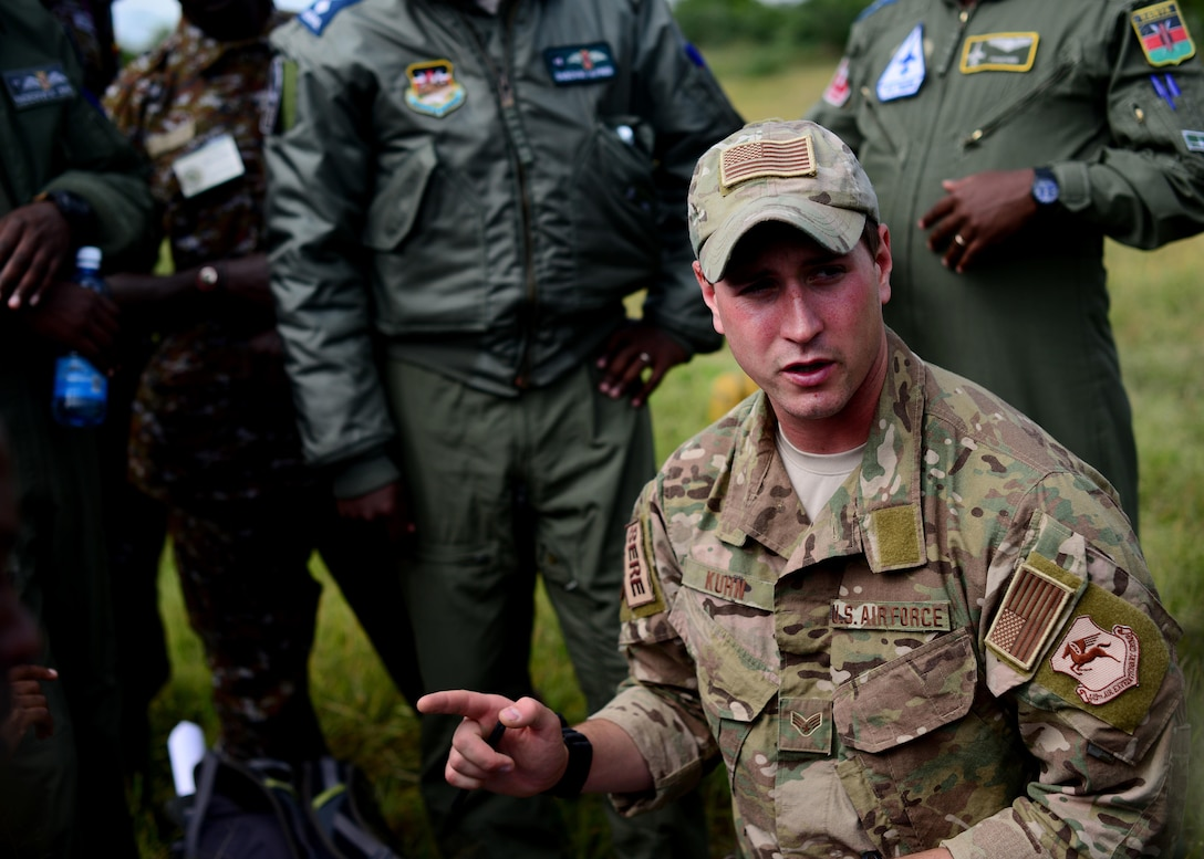 U.S. Air Force Senior Airman Ian Khun, 82nd Expeditionary Rescue Squadron, survival evasion resistance and escape specialist, discusses land navigation instruction with Kenyan Defense Force members at Laikipia Air Base, Kenya, June 23, 2016. More than 50 U.S. Air Force Airmen participated in the first African Partnership Flight in Kenya. The APF is designed for U.S. and African partner nations to work together in a learning environment to help build expertise and professional knowledge and skills in key areas such as personnel recovery command and control, survival and evasion principles and tactical combat casualty care.  (U.S. Air Force photo by Tech. Sgt. Evelyn Chavez/Released)