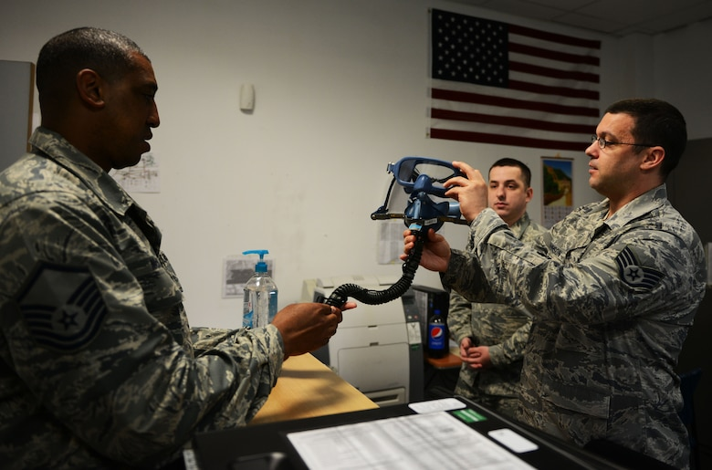 Staff Sgt. Jacob Johnson, 313th Expeditionary Operations Support Squadron aircrew flight equipment member, explains the features of a quick-don mask to Master Sgt. Robert McNeal, 313th EOSS superintendent, at Ramstein Air Base, Germany, June 21, 2016. AFE is responsible for providing life support equipment to Air Mobility Command aircrew transiting through Ramstein en route to deployed locations. (U.S.  Air Force photo/ Airman 1st Class Joshua Magbanua)
