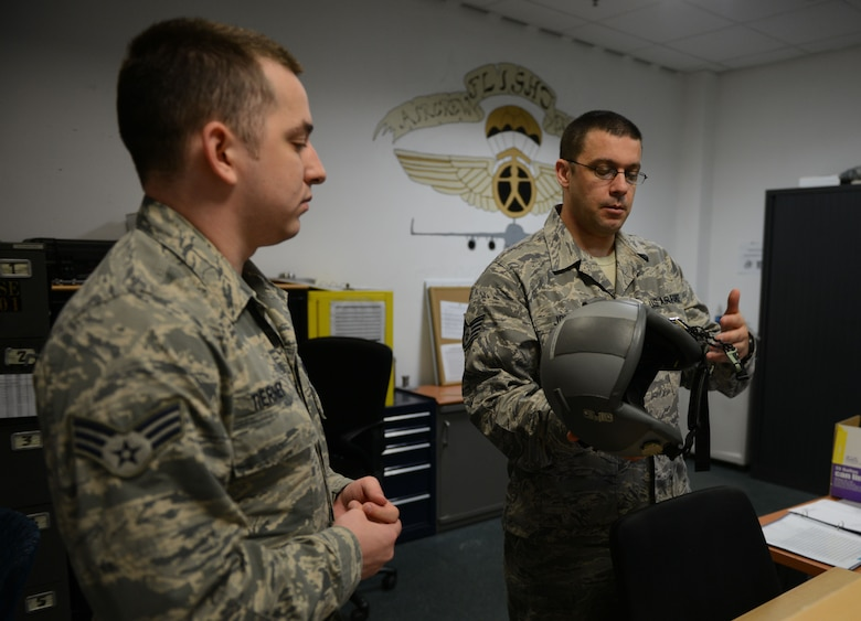 Staff Sgt. Jacob Johnson and Senior Airman Casey Tierney, 313th Expeditionary Operations Support Squadron aircrew flight equipment members, explain the features of a flight helmet at Ramstein Air Base, Germany, June 21, 2016. Both Johnson and Tierney are deployed to Ramstein as part of the 313th EOSS from Dover Air Force Base.  (U.S.  Air Force photo/ Airman 1st Class Joshua Magbanua)