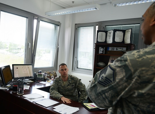 Lt. Col. Lucas Jobe, 313th Expeditionary Operations Support Squadron commander, receives a briefing from Master Sgt. Robert McNeal, 313th EOSS superintendent, at Ramstein Air Base, Germany, June 21, 2016. The 313th EOSS supports Air Mobility Command aircrew transiting through Ramstein en route to deployed locations. (U.S.  Air Force photo/ Airman 1st Class Joshua Magbanua)
