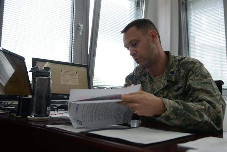 Lt. Col. Lucas Jobe, 313th Expeditionary Operations Support Squadron commander, sifts through documents at Ramstein Air Base, Germany, June 21, 2016. The 313th EOSS is a total force integrated unit consisting of active-duty, reserve and Air National Guard personnel. (U.S.  Air Force photo/ Airman 1st Class Joshua Magbanua)