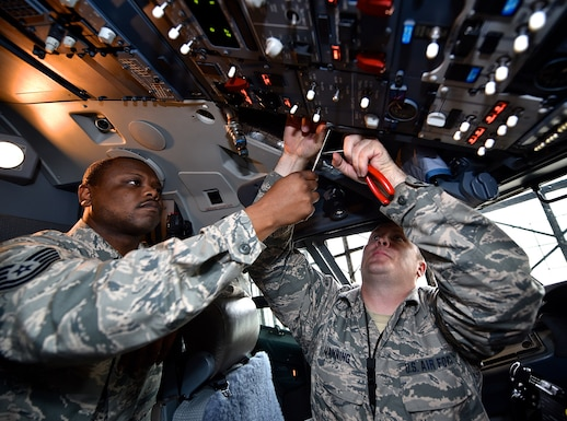 Tech. Sgt. Aaron Flanigan, left, an avionics tech with the 932nd Aircraft Maintenance Squadron assists Tech. Sgt. Billy Manning, sheets metal worker with the 932nd Maintenance Squadron to repair an overheated heads up display and replace a nut plate, May 2, 2016, Scott Air Force Base, Illinois.  (U.S. Air Force photo by Christopher Parr)