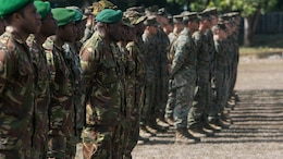 Papua New Guinea soldiers and U.S. Marines and Sailors stand in formation during the opening remarks for Exercise Koa Moana, June 18, 2016, at Taurama Barracks, Papua New Guinea. The multi-national, bilateral exercise is designed to improve interoperability and relations through mil-to-mil training and by sharing infantry, engineering, medical and law enforcement skills.